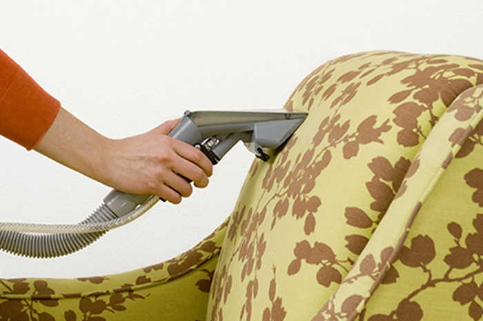 Man cleans upholstery.